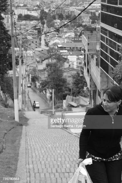 Woman Looking Away While Walking On Steps Outdoors