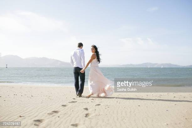 woman looking back while strolling hand in hand with boyfriend on beach - long dress stock pictures, royalty-free photos & images