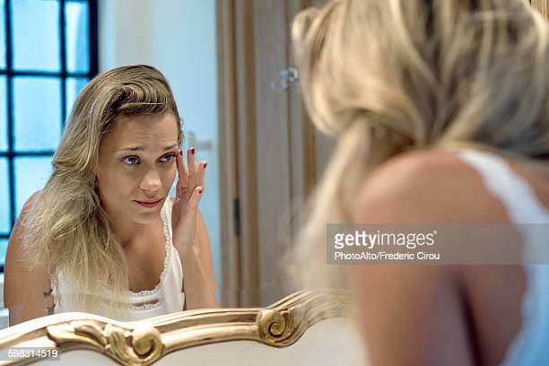 Woman looking bleary-eyed at self in bathroom mirror