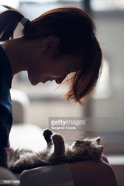 Woman looking down at kitten