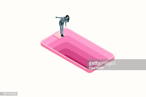 woman looking down deep hole in large pink smart phone - facebook stock pictures, royalty-free photos & images