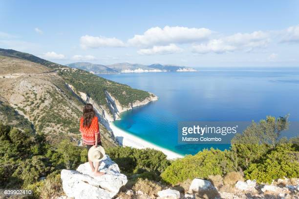 woman looking down to myrtos beach, kefalonia, greek islands, greece - mediterranean sea stock pictures, royalty-free photos & images