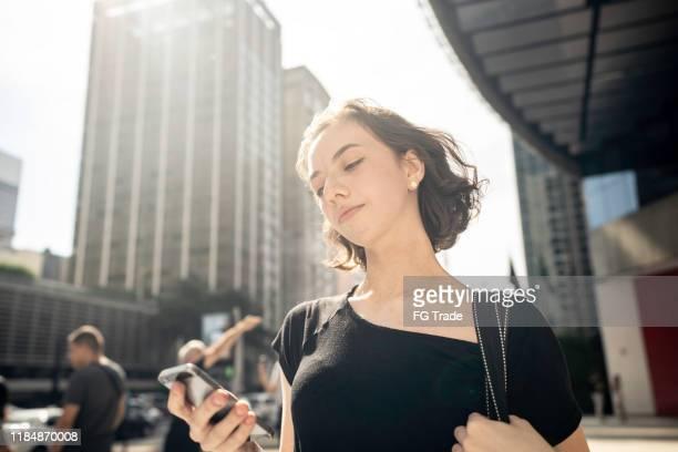 下を見ている女性、スマートフォンを使って - アベニュー ストックフォトと画像