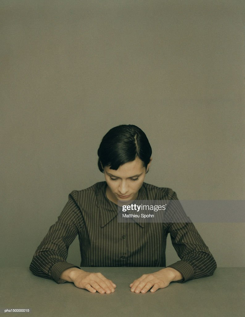 Woman looking down with arms extended forward and resting on table, portrait : Stockfoto