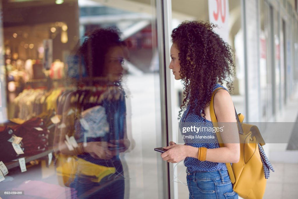 A woman looking excited through a store window : Stock Photo