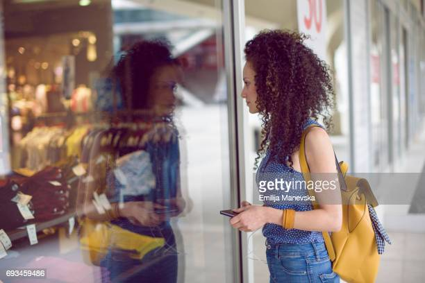 A woman looking excited through a store window