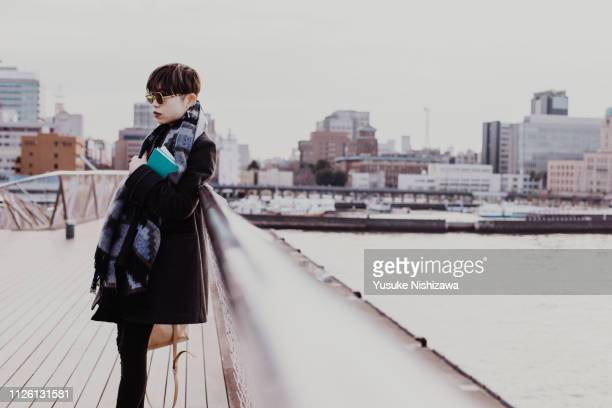 a woman looking far away - yusuke nishizawa stock-fotos und bilder