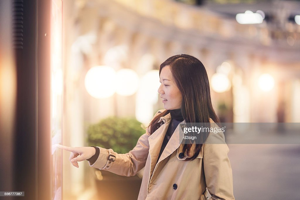 Woman looking for directions with a digital kiosk : Stock Photo