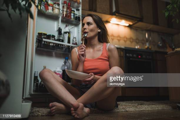woman looking for midnight snack in the refrigerator - midnight stock pictures, royalty-free photos & images