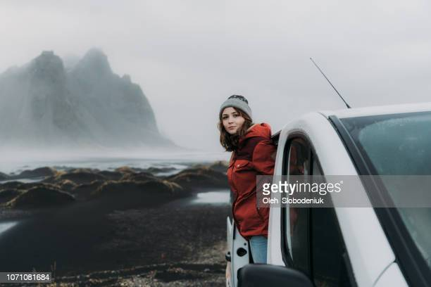 woman looking from car near  vestrahorn mountains near the sea - dramatic landscape stock pictures, royalty-free photos & images