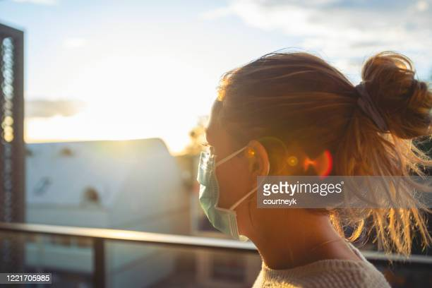 woman looking from her balcony at sunset. - lockdown foto e immagini stock