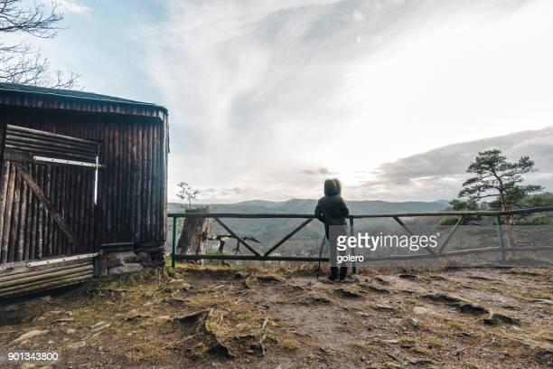 Frau, die vom Aussichtspunkt ins land