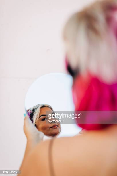 woman looking her reflection in hand mirror - fat blonde women stock pictures, royalty-free photos & images