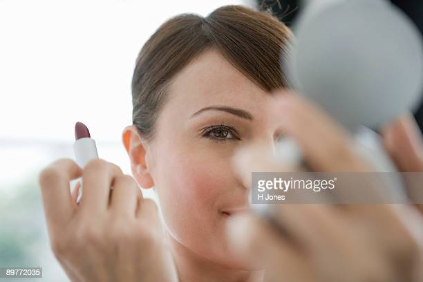Woman looking in a cosmetic mirror.