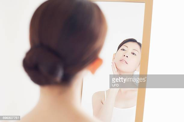 a woman looking in a mirror - full length mirror stock photos and pictures
