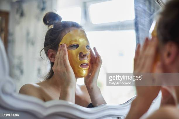 woman looking in a mirror putting a face mask on - indulgence stock pictures, royalty-free photos & images