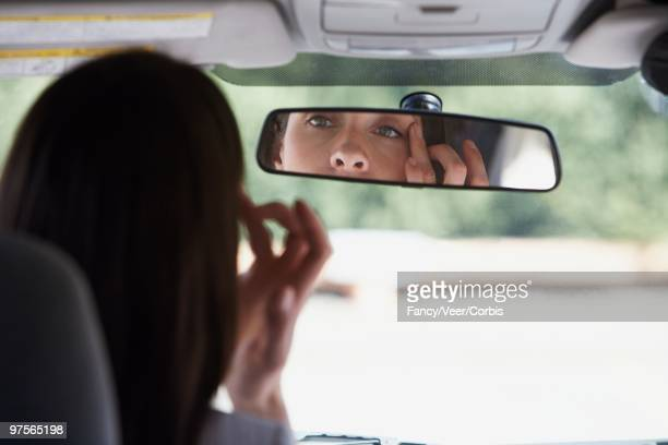 Woman Looking in a Rear View Mirror