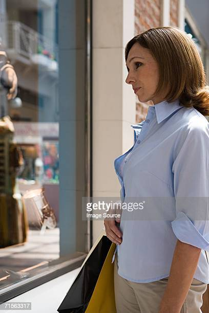 woman looking in a shop window - alleen één oudere vrouw stockfoto's en -beelden
