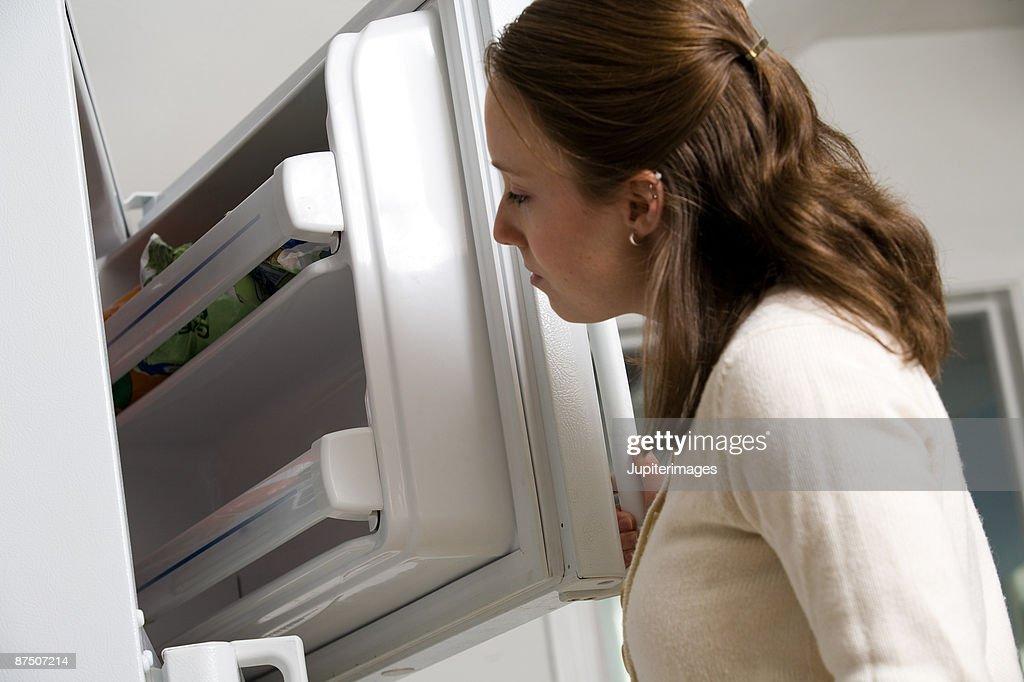 Woman looking in freezer : Stock Photo