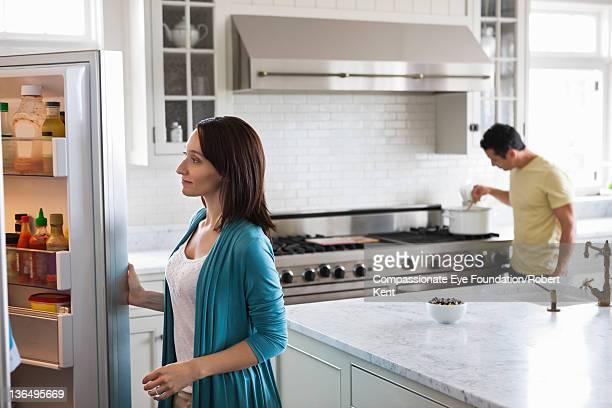 Woman looking in fridge in modern kitchen