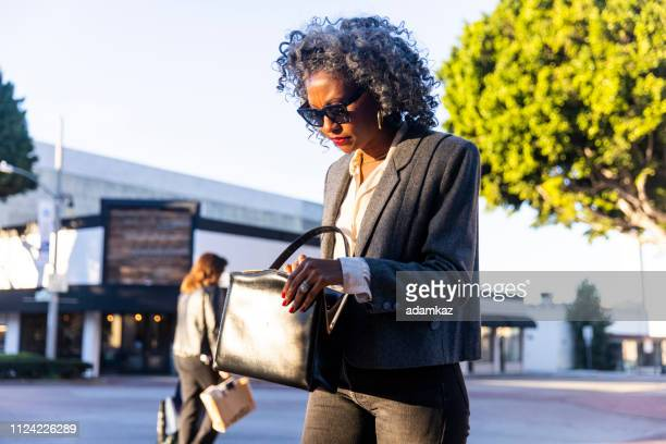 woman looking in her purse - black purse stock pictures, royalty-free photos & images
