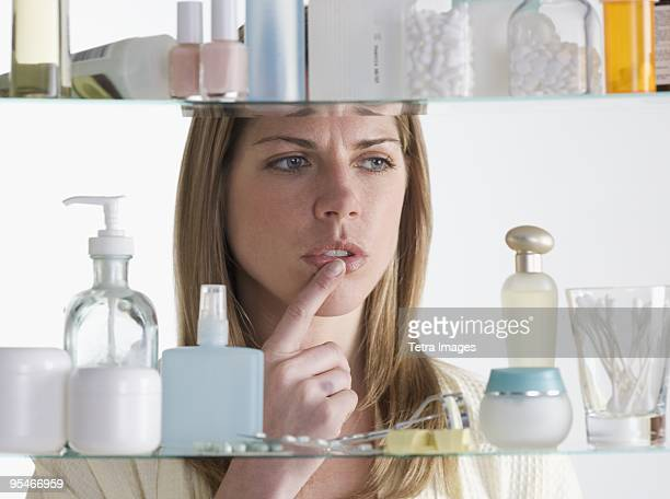 woman looking in medicine cabinet - medicine cabinet stock pictures, royalty-free photos & images