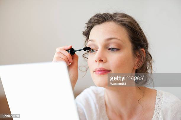 Woman looking in mirror applying mascara