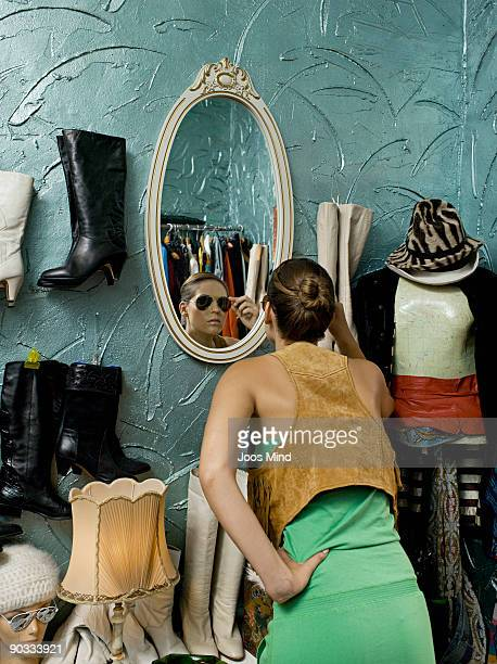 woman looking in mirror in second-hand store