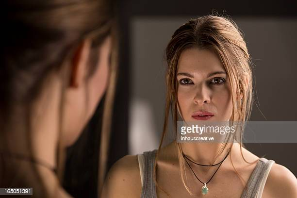woman looking in mirror - mirror stock photos and pictures