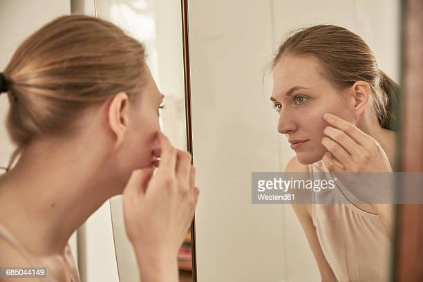 woman looking in mirror - woman in mirror stock photos and pictures