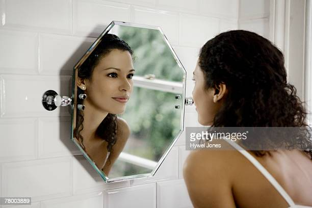 Woman looking in mirror.