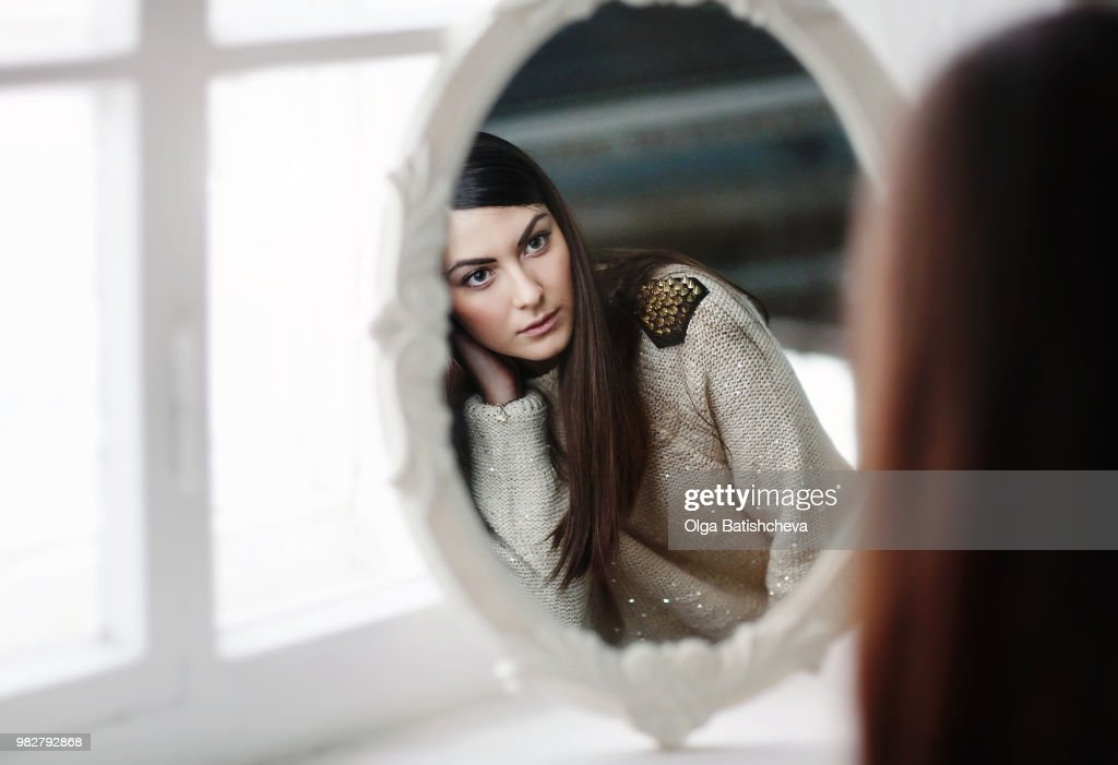 Woman looking in mirror : Stock Photo
