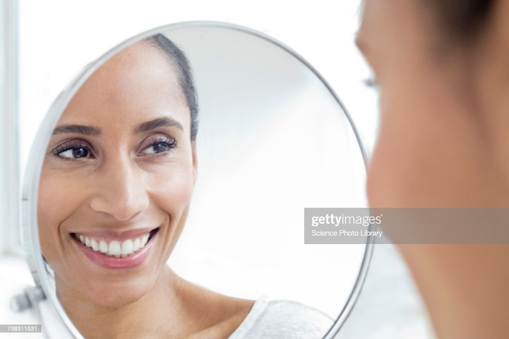 Woman looking in mirror, smiling : Stock Photo