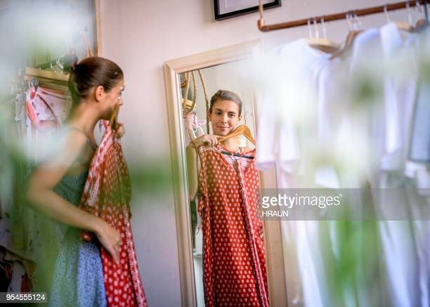 woman looking in mirror while trying dress in room in a store. - dress stock pictures, royalty-free photos & images