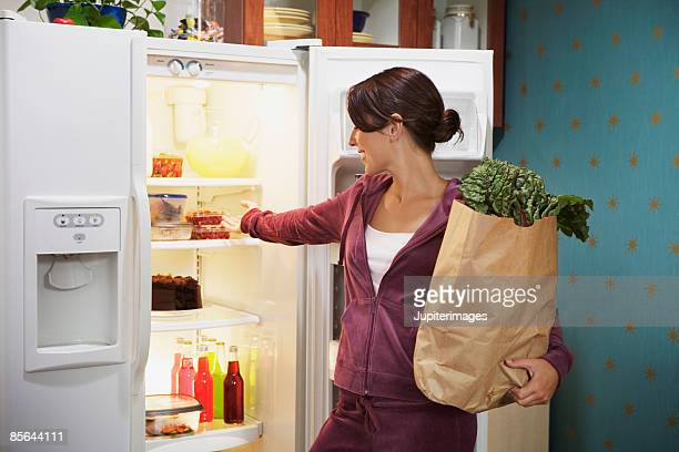 Woman looking in refrigerator and holding grocery bag