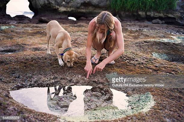Woman looking in rock pool, dog beside her, Nusa Ceningan, Indonesia