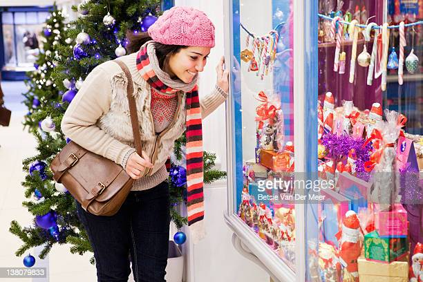 woman looking in shop window at chocolate display. - sweet shop stock pictures, royalty-free photos & images