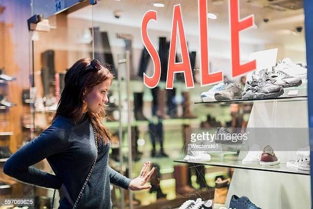 woman looking in shop window of a shoe shop - sale stock photos and pictures