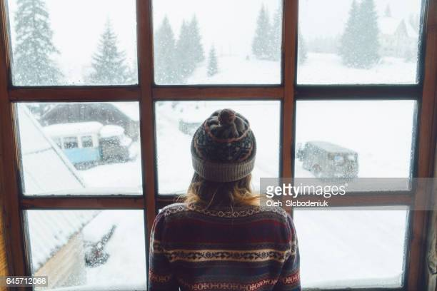 woman looking in the window in winter - winter weather stock photos and pictures