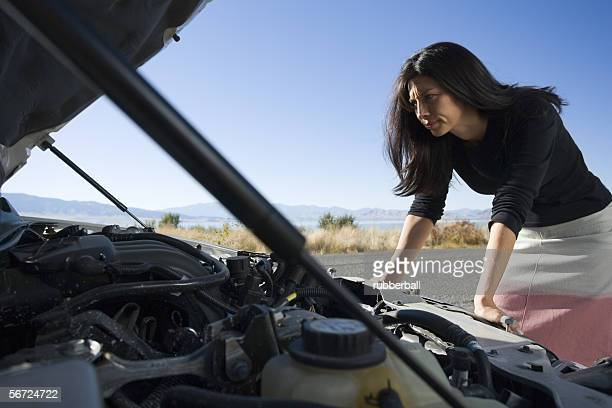 Woman looking inside a car engine