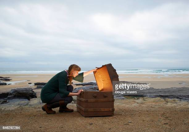 Woman looking inside treasure chest on deserted beach.