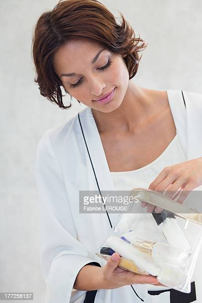 Woman looking into a makeup bag