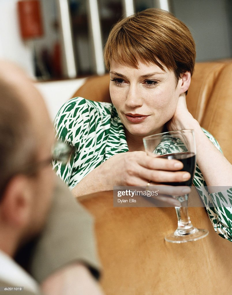 Woman Looking Into a Man's Eyes and Holding a Glass of Red Wine : Stock Photo