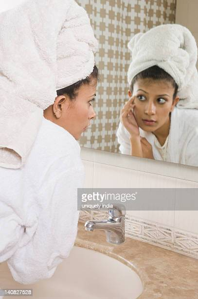 woman looking into a mirror - one young woman only stock pictures, royalty-free photos & images