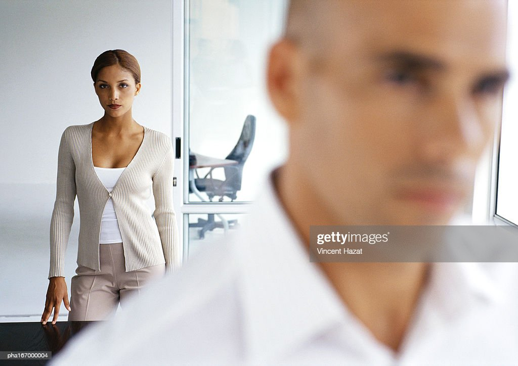 Woman looking into camera, man in blurred foreground : Stockfoto