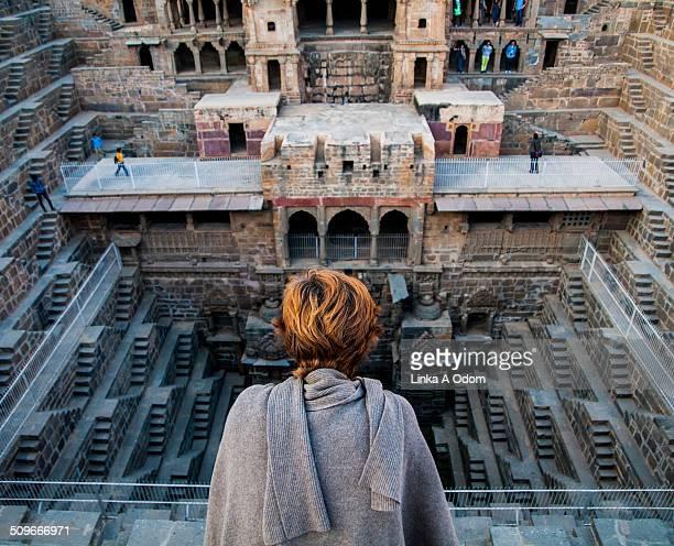 A woman looking into Chand Baori stepwell.