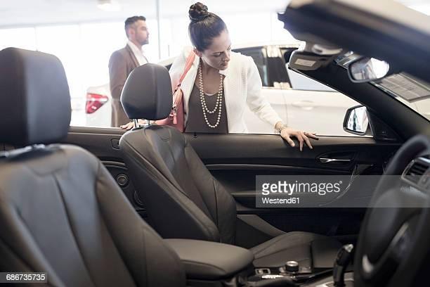 Woman looking into convertible at car dealership