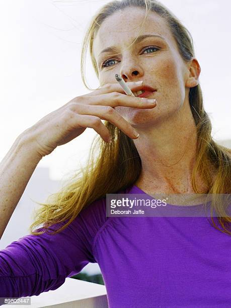 Woman looking into distance while smoking