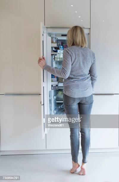woman looking into fridge - descalço imagens e fotografias de stock