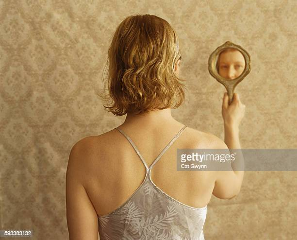 woman looking into hand mirror - hand mirror stock pictures, royalty-free photos & images
